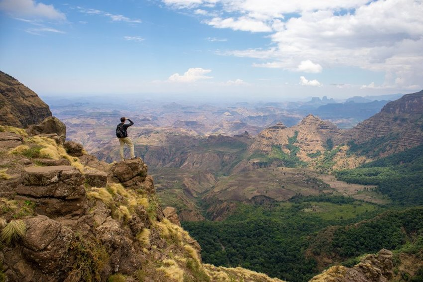 Hiker on cliff's edge showing distant view of valleys and mountain peaks in Ethiopia