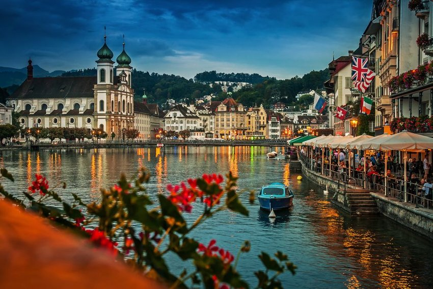Scenic waterway and old-fashioned architecture in Lucerne, Switzerland, seen during the evening