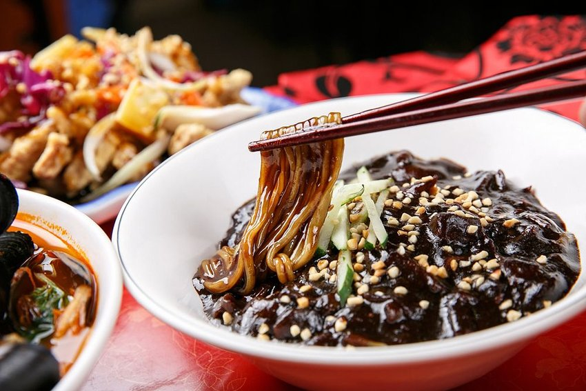 Traditional bowl of jajangmyeon black bean noodles being lifted with chopsticks