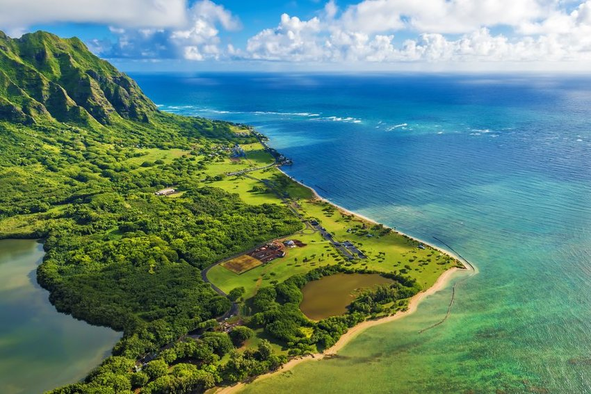 Aerial view of Kualoa Point at Kaneohe Bay, Hawaii, showing blue water and cloudy skies