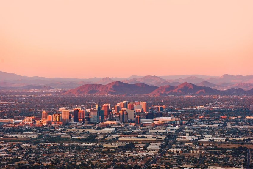 Aerial view of downtown Phoenix Arizona, showing sunset colors and distant mountains