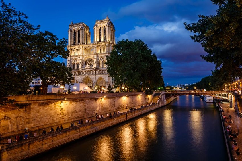 Night view of the Notre Dame de Paris Cathedral under dark blue skies, France