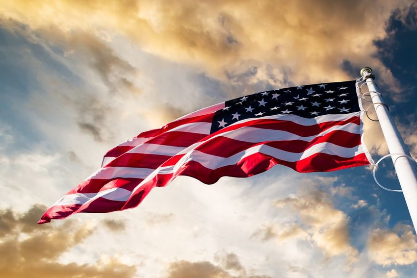Dramatic view of waving United States flag seen against cloudy sky background