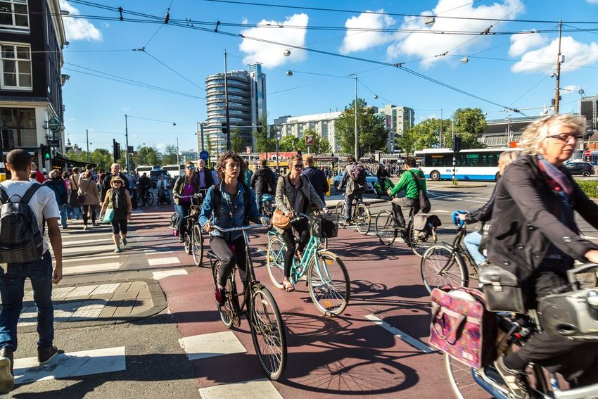 Group of Dutch people ride their bikes across a busy city street under clear skies