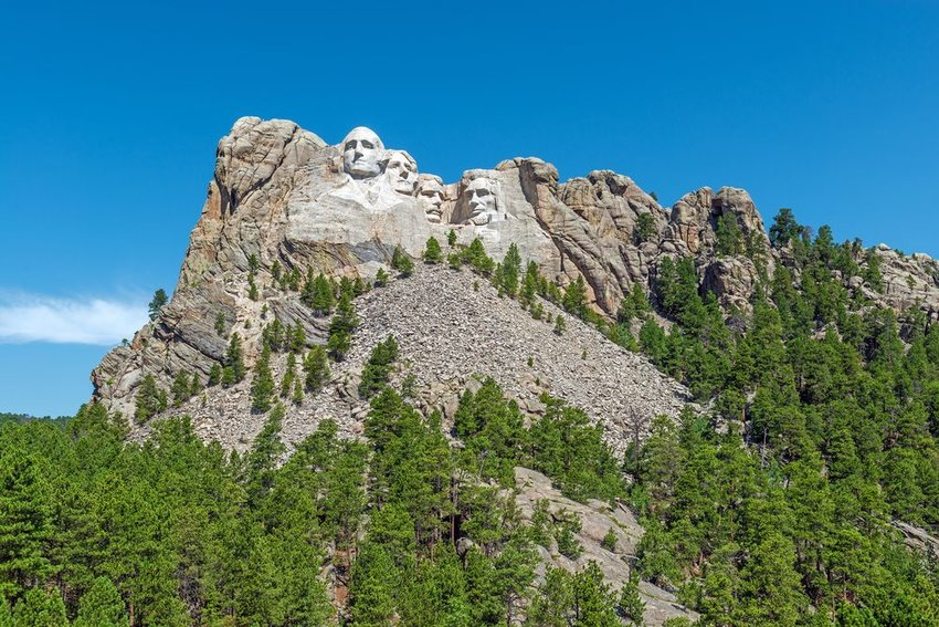 Distant view of Mount Rushmore monument, showing forests and Black Hills region in South Dakota