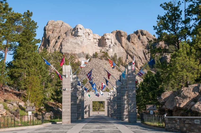 Street view of entrance to Mount Rushmore park, showing flags and distant monument