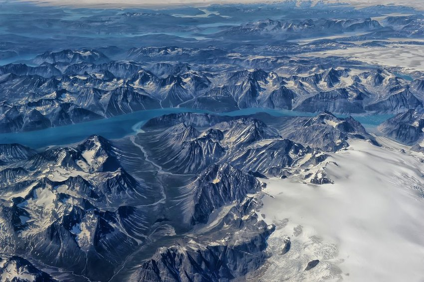 Aerial view of Greenland landscape, showing large snowcapped hills and rocky outcroppings