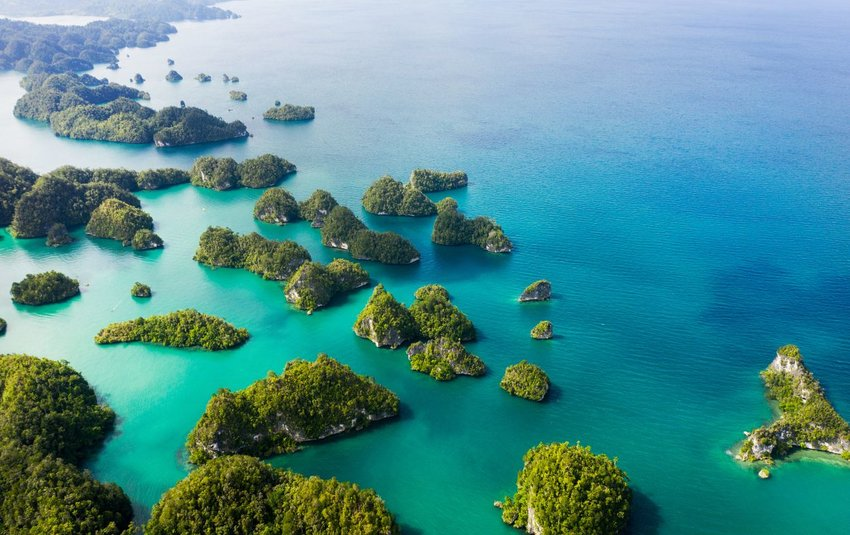 Aerial shot of beautiful green islands in the vast oceans of Indonesia