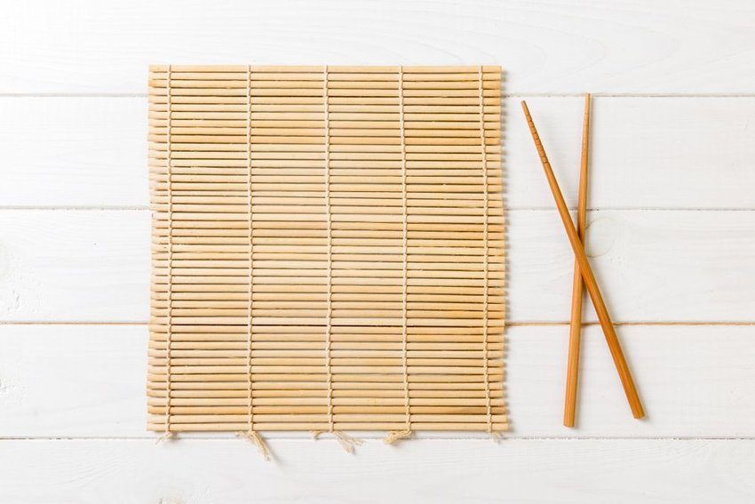 Pair of chopsticks next to an empty bamboo mat on a white background