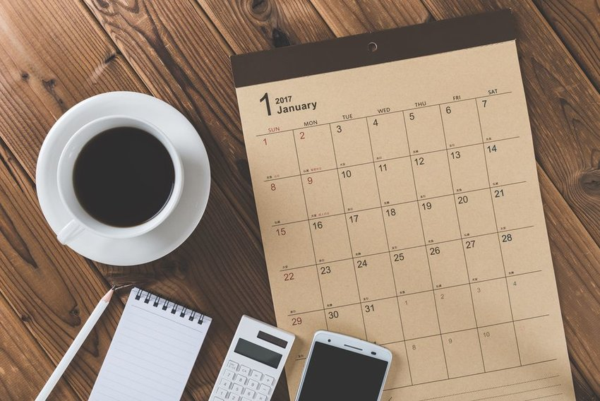 Calendar with notes and coffee on wooden table