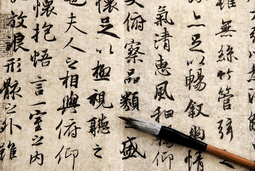 Paintbrush resting on a piece of paper with Chinese writing