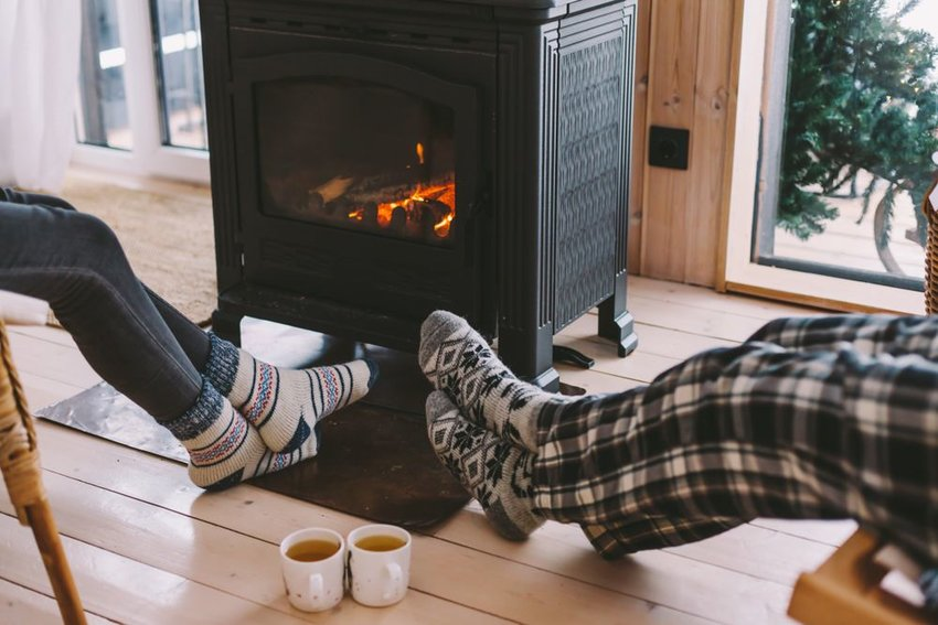 Couple with feet in front of fireplace and mugs of tea on wood floor