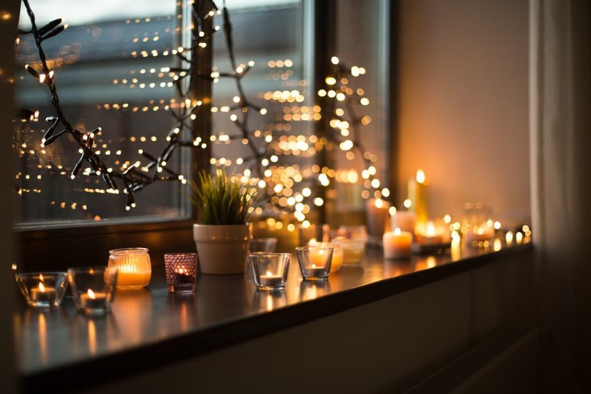 String lights hanging on window with candles and a plant on the window sill