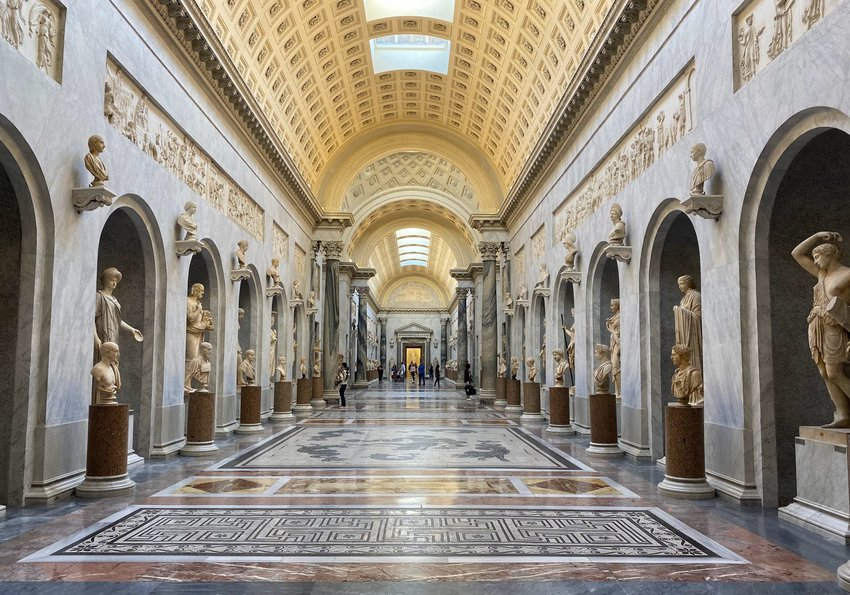 Inside the Vatican Museums with designs on the tiled floor and statues lining a hallway in Vatican City