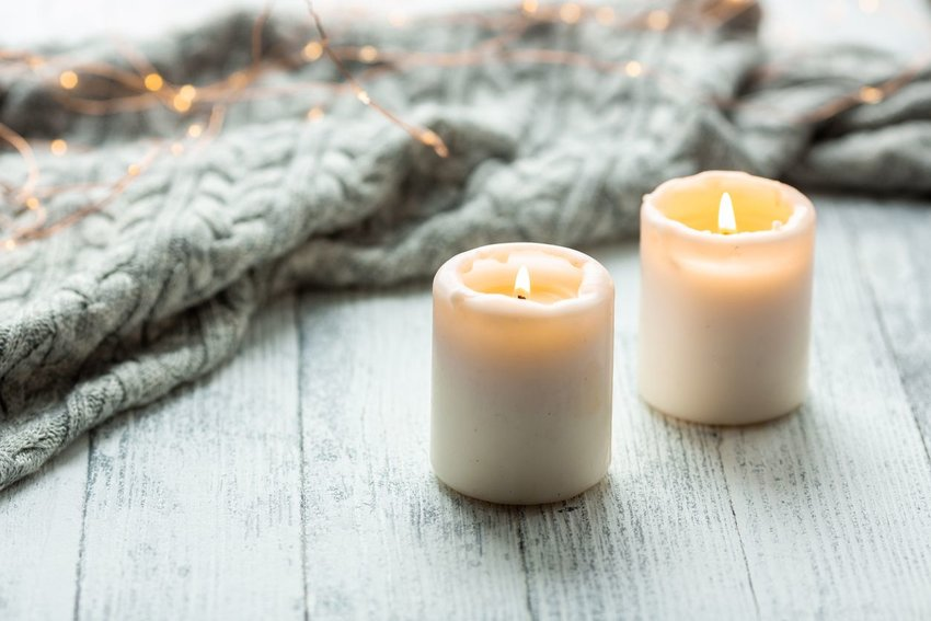 Two candles lit on the floor with a blanket and string lights in the background