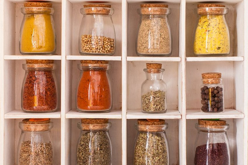 Glass containers of spices neatly displayed on shelves