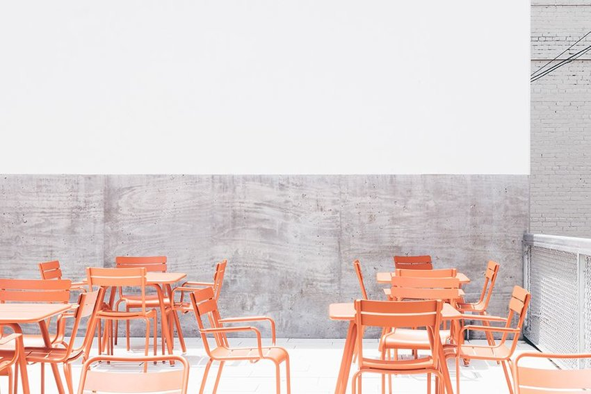 Bright coral colored outdoor dining tables and chairs