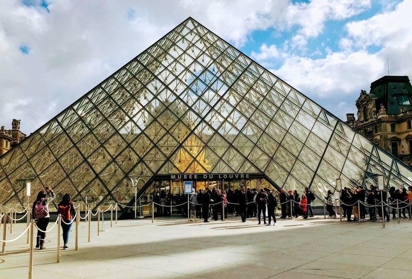 Exterior of The Louvre with people waiting in line to go inside
