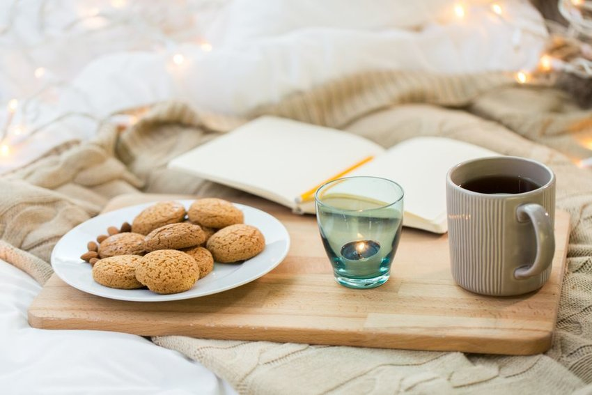 Plate of cookies with a candle and tea on a wooden tray