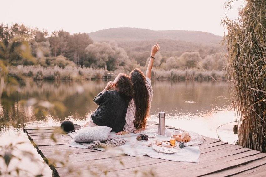 Two people sitting at the edge of a dock with a picnic set up