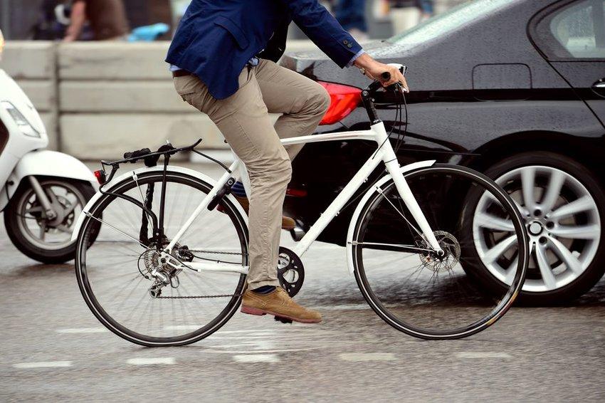 Person riding white bike on street next to car
