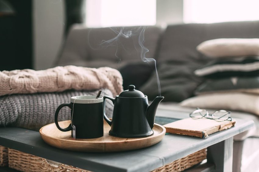 Cup of tea and teapot steaming on table with pillows and blankets in background