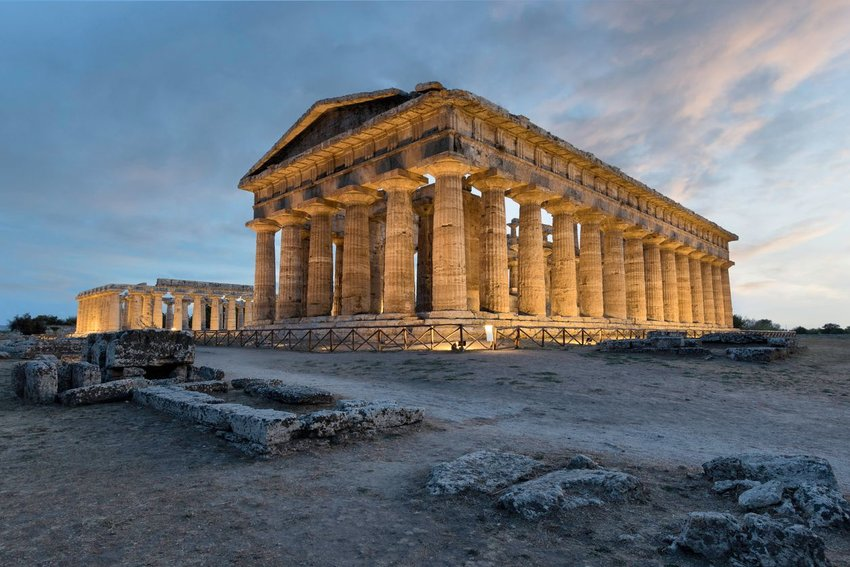 Ruins of Paestum in Italy at sunset with lights on the structure
