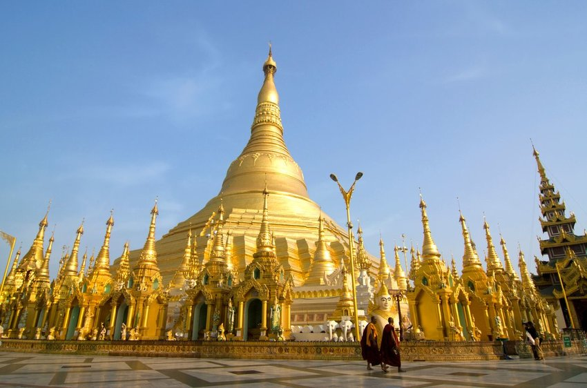 Shwedagon Pagoda temple in Myanmar with two monks walking in front