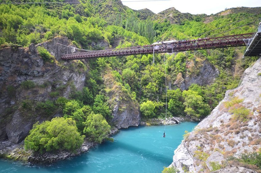 Person bungee jumping off a bridge over bright blue water