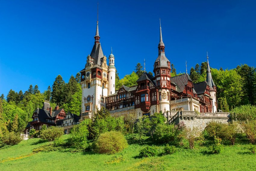 Peleş Castle in Sinaia, Romania surrounded by greenery