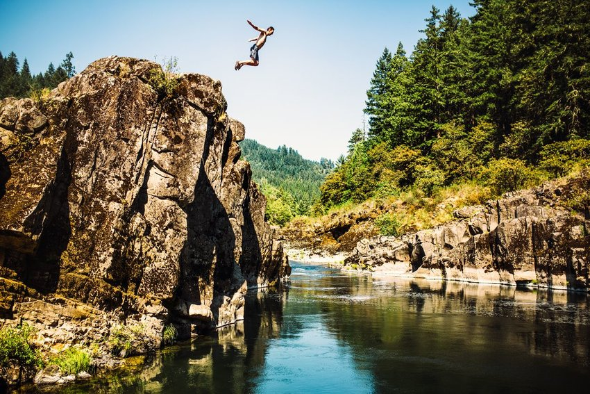 Person cliff jumping off a big rock formation with trees in the background