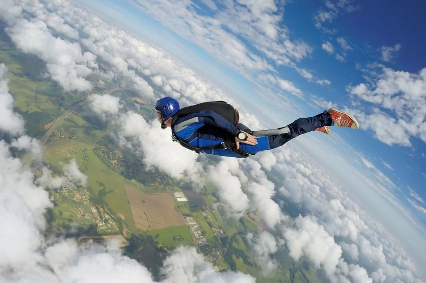 Person skydiving over the clouds