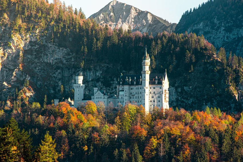 Neuschwanstein Castle under a cliff edge surrounded by colorful trees in Schwangau, Germany