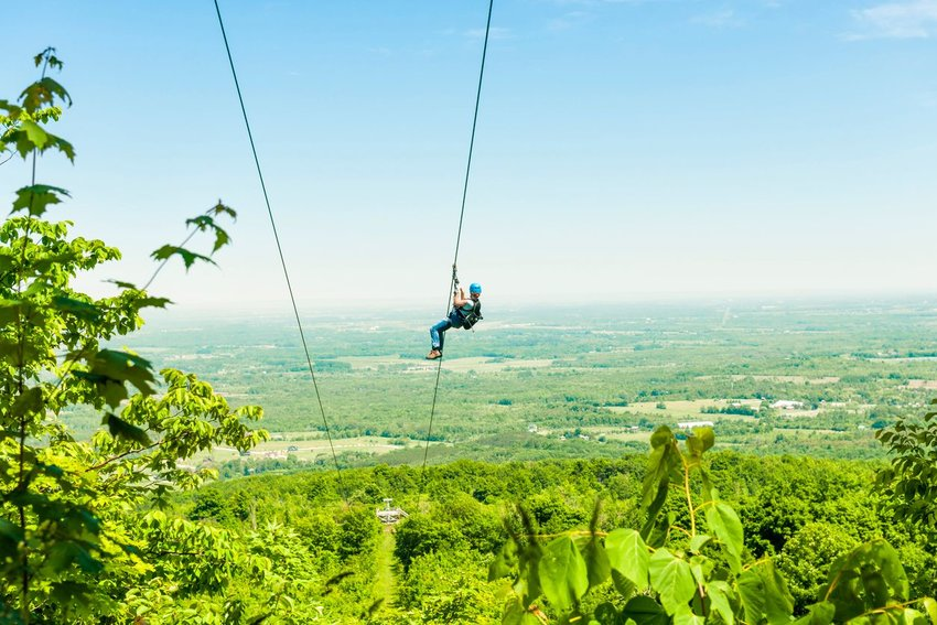 Person with a blue helmet zip lining over a green jungle