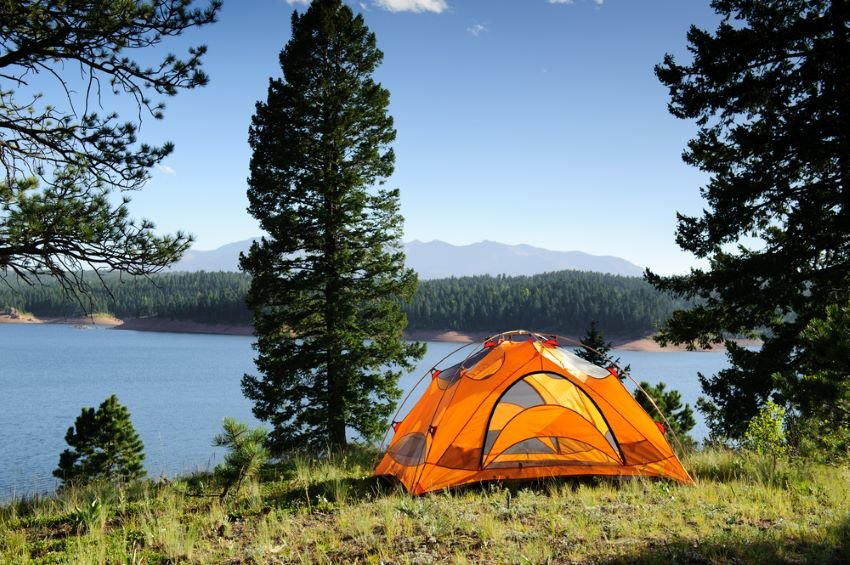 Tent set up by lake in the mountains.