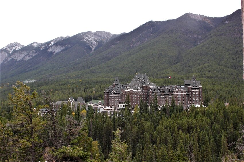 Fairmont Banff Springs hotel in the distance, surrounded by mountains and forest