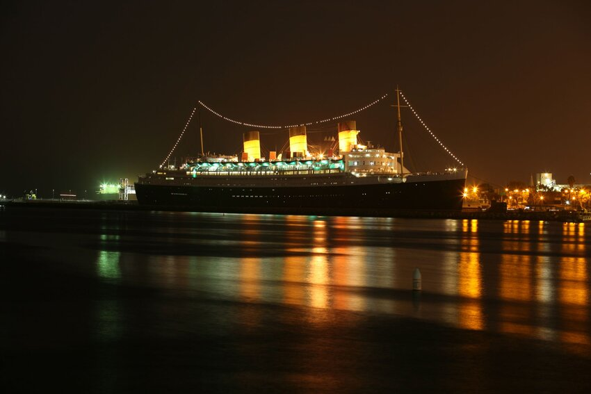 View of Queen Mary ship at night across the port