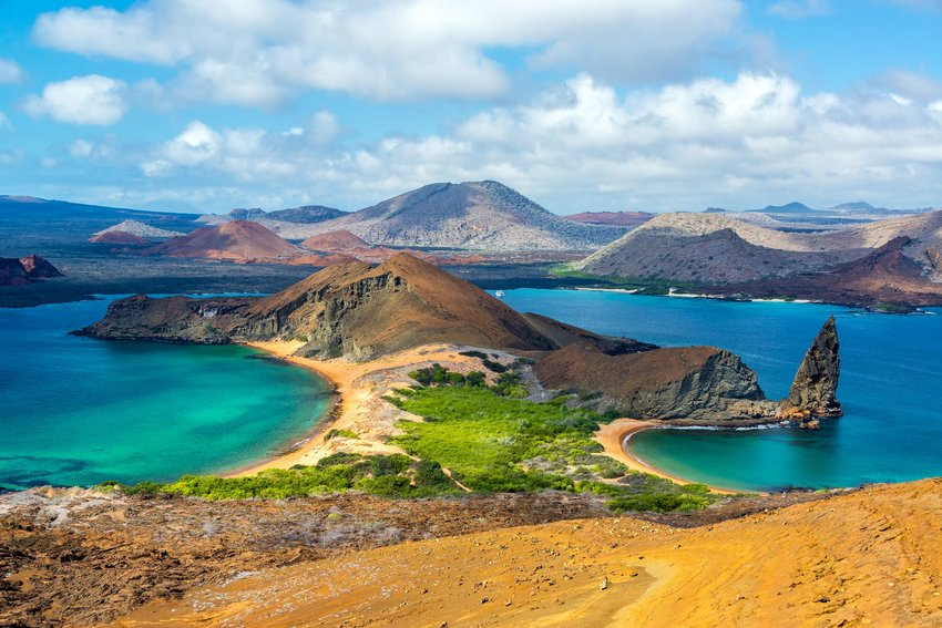Looking down at mountains, beaches, and blue waters of Bartolome Island