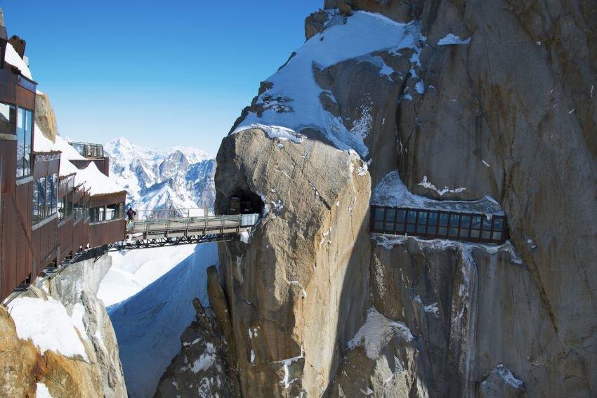 Aiguille du Midi Bridge stretches over snow-capped mountain peaks.