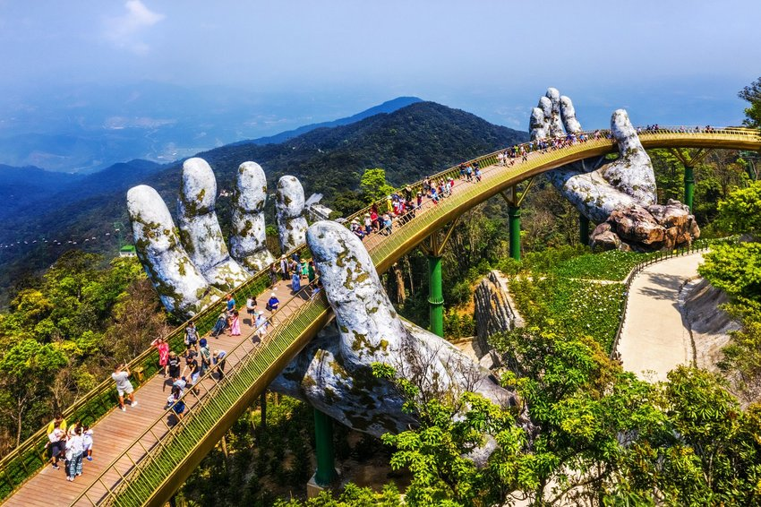 Two giant stone hands hold up the Golden Bridge above Vietnam mountains