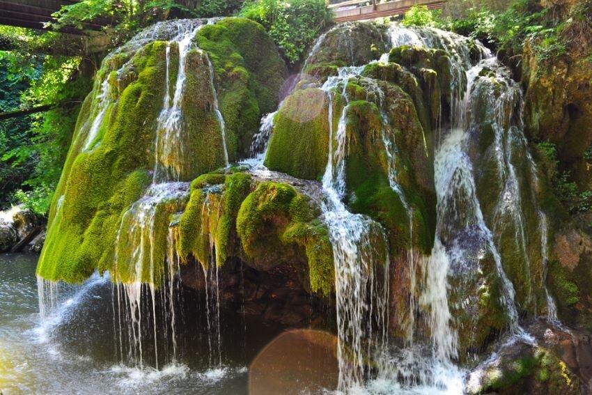 Mushrooom-shaped and brilliant green Bigăr Waterfall.