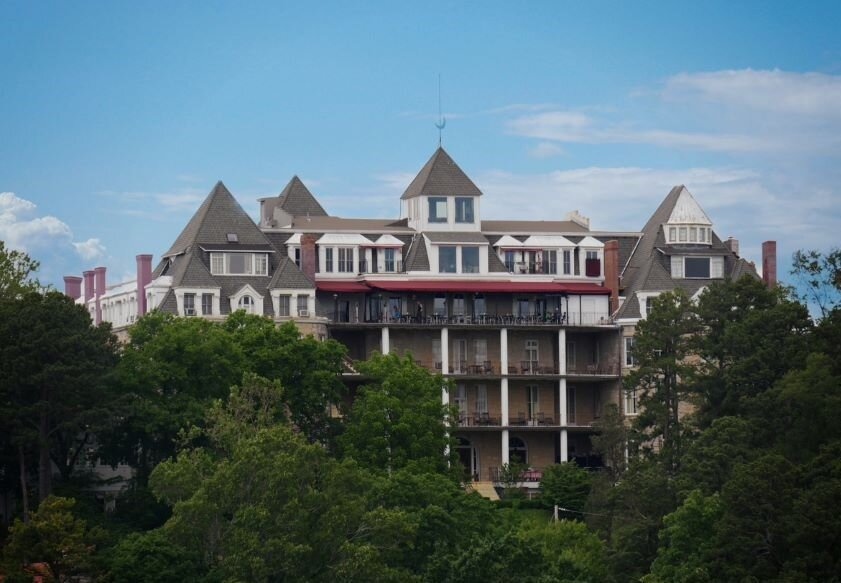The Crescent Hotel in Eureka Springs behind trees.