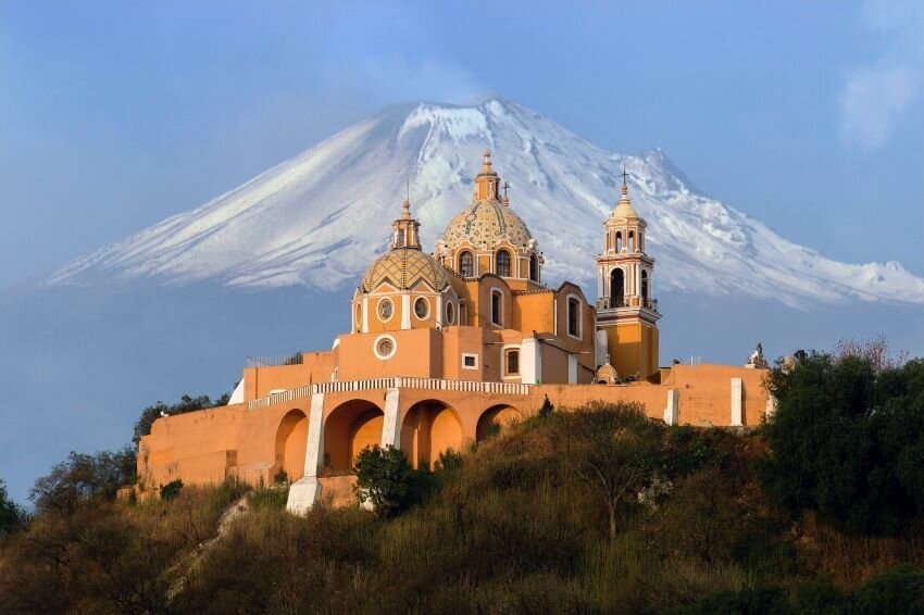 Great Pyramid of Cholula in front of snow covered mountain.