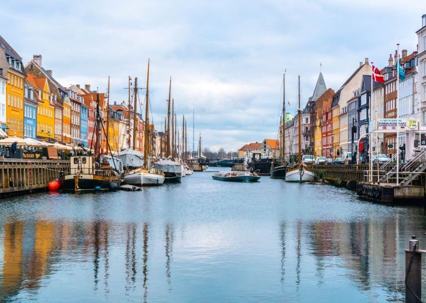 Boats in the river in Copenhagen with colorful row houses behind.