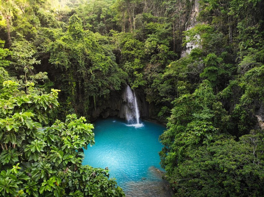 Aerial view of Kawasan Falls with vivid turquoise pool and lush forest surrounding