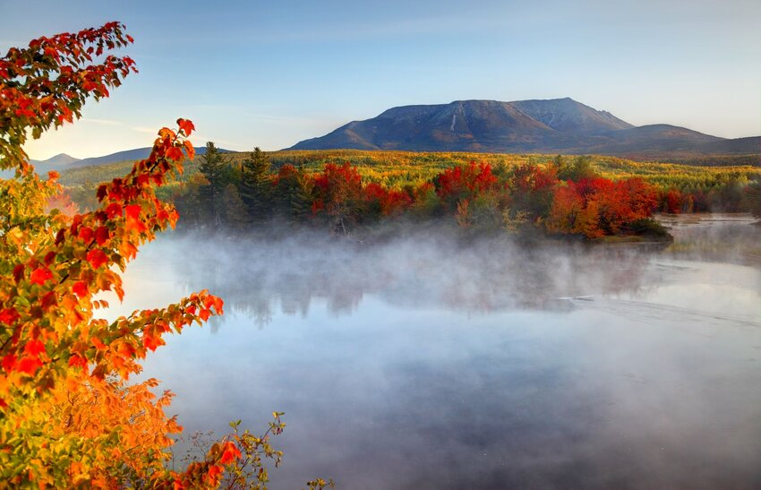 Mount Katahdin in background of Baxter State Park with fog-covered lake and autumn trees