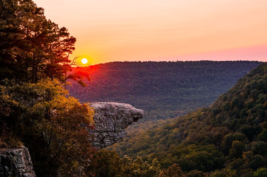 Hawksbill Crag rock formation juts out above hilly landscape with sun setting behind