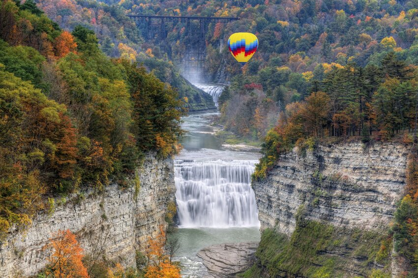 Hot air balloon over dramatic waterfall and fall leaves at Letchworth State Park