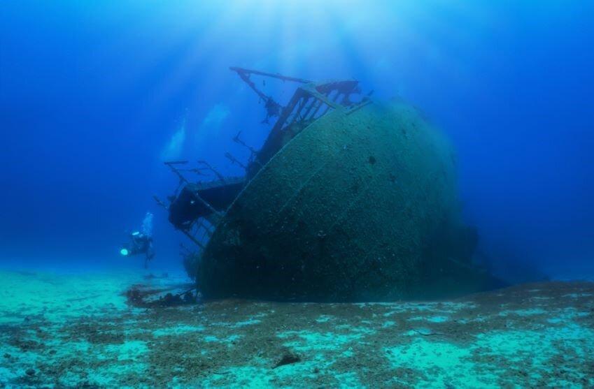 A sunken shipwreck in the Mediterranean Sea with a scuba diver, Greece.