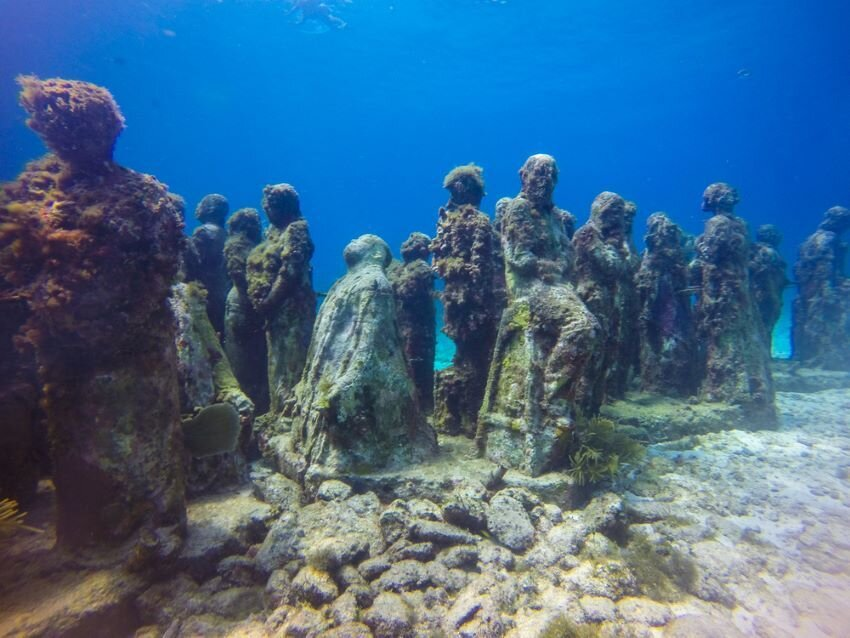 Statues situated under the ocean.